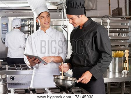 Male chef with digital tablet assisting colleague in preparing food at kitchen