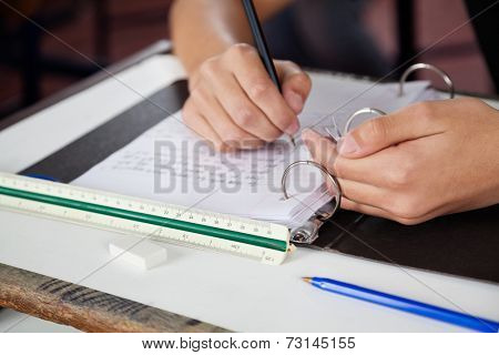 Cropped image of teenage schoolboy copying at desk during examination