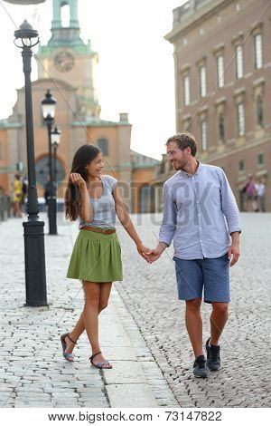 Stockholm couple walking romantic by Royal Palace. Young woman and man holding hands walking in Swedish street in Gamla Stand the old town of Stockholm, Sweden.