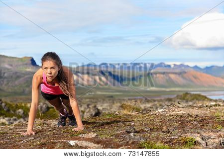 Push-ups fitness woman doing pushups or plank outside in amazing nature landscape on Iceland. Fit female sport model girl training crossfit outdoors. Mixed race Asian Caucasian athlete in her 20s.