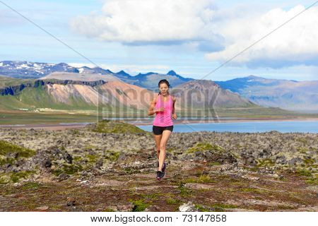 Runner woman trail running in nature. Female fitness girl athlete cross country trail running in amazing nature landscape outside. Image from Iceland.