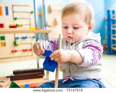 cute little girl in the classroom early development plays with numerous  toys