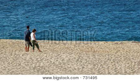 Couple Standing On Beach With Blue Blue Ocean