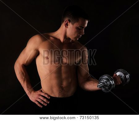 Athletic man execute exercise with dumbbells, on black background