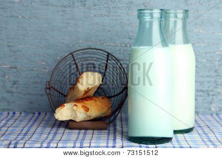 Retro bottles of tasty milk and bread, on table