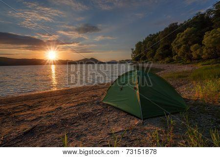 green tent on lake coastline closeup