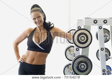 Portrait of woman next to rack of free weights