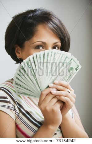 Hispanic woman holding fanned out US currency