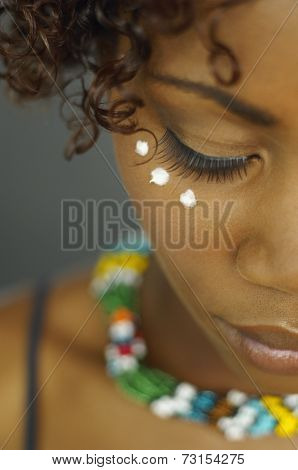 Close up of African woman with dots of cream under eye