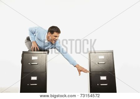 Businessman on top of filing cabinet reaching for other filing cabinet