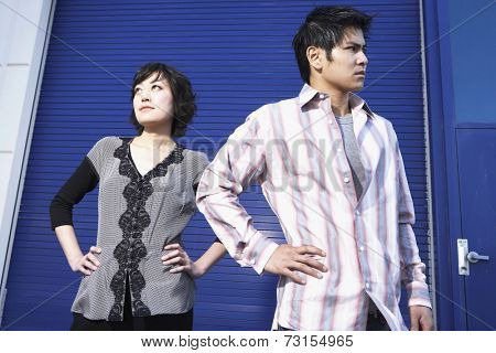 Portrait of young couple with hands on hips