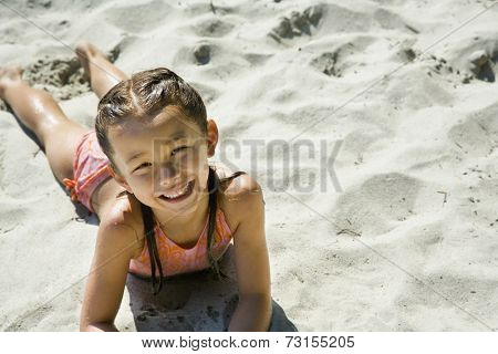 Asian girl laying in sand