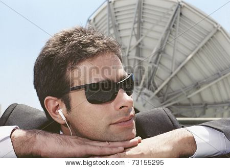 Hispanic man wearing earbuds next to satellite dish