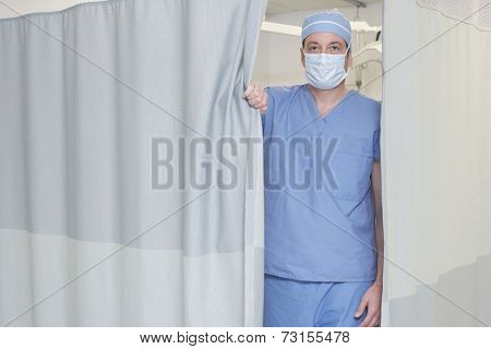 Male doctor opening privacy curtain
