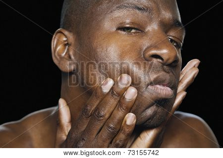 African man with hands on face