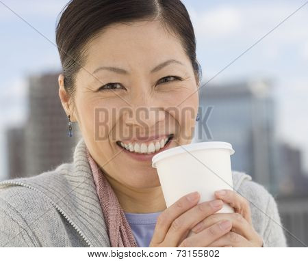 Middle-aged Asian woman holding coffee cup outdoors