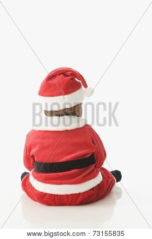 Rear view studio shot of baby wearing Santa Claus outfit