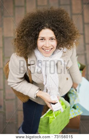Hispanic woman holding cell phone and shopping bags