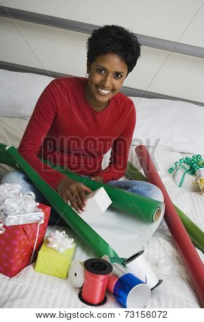 Indian woman wrapping gifts on floor