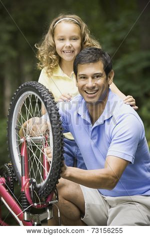 Hispanic father fixing daughter's bicycle