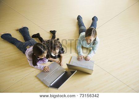 Three girls looking at laptops on floor