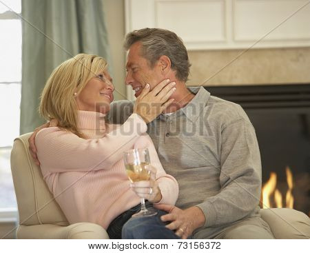 Couple smiling at each other in armchair