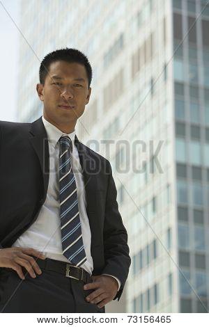 Portrait of Asian businessman in front of sky scraper
