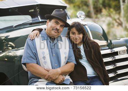 Hispanic father and daughter sitting on classic car