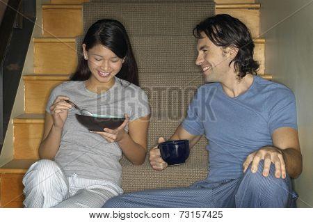 Multi-ethnic couple having breakfast on stairs