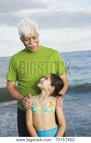 Hispanic grandfather and granddaughter at beach