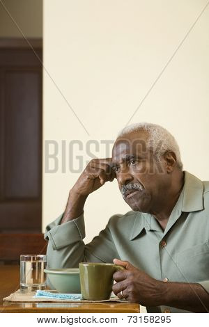 Senior African man at breakfast table