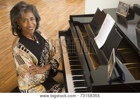 Senior African woman sitting at piano