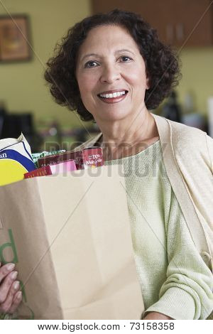 Senior African woman carrying grocery bag