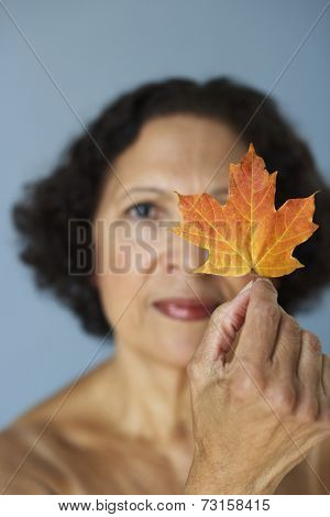 Senior African woman holding autumn leaf over eye