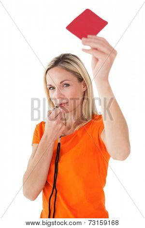 Portrait of mature woman blowing whistle and holding red card on white background