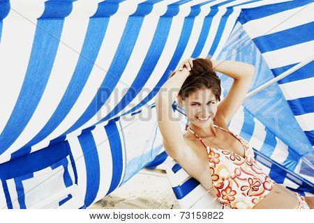 Young woman sitting under beach sun shade