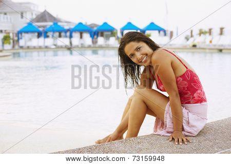 Hispanic woman sitting next to swimming pool