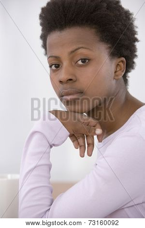 African woman resting chin on hand
