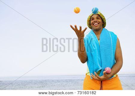 Hispanic man juggling at beach