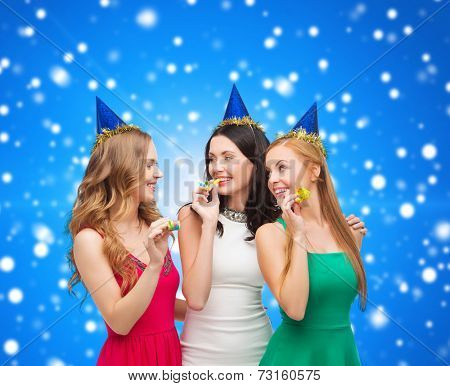 holidays, people and celebration concept - smiling women in party caps blowing to whistles over blue snowing background