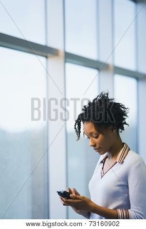 African businesswoman dialing cell phone