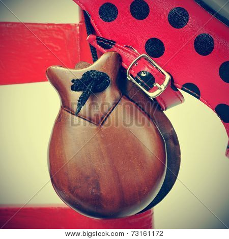 closeup of a pair of castanets and a typical dot-patterned red flamenco shoe