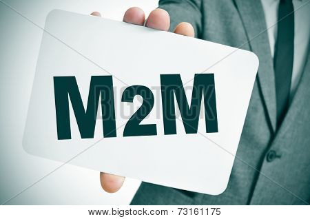 a businessman showing a signboard with the text M2M, for the machine to machine technologies, written in it