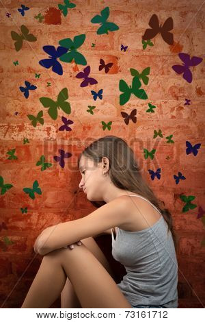 Romantic and nostalgic teenage girl sitting on the floor with colorful butterflies on a brick wall