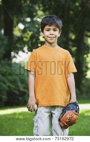 Hispanic boy with baseball glove and ball
