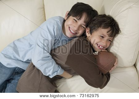 Hispanic brothers hugging with football