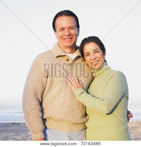 Hispanic couple hugging at beach