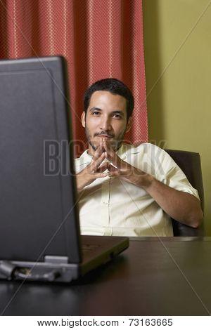 Hispanic man sitting at desk with laptop