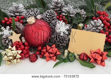 Christmas bauble decorations, gift tag, holly and winter greenery over snow background.