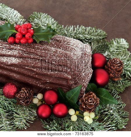 Chocolate yule log with red bauble decorations, holly, ivy, mistletoe and snow covered fir.